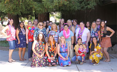 Large group photo of team members dressed in Hawaiian clothing