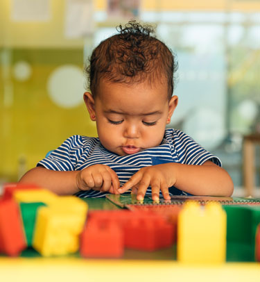 A toddler plays with building blocks.