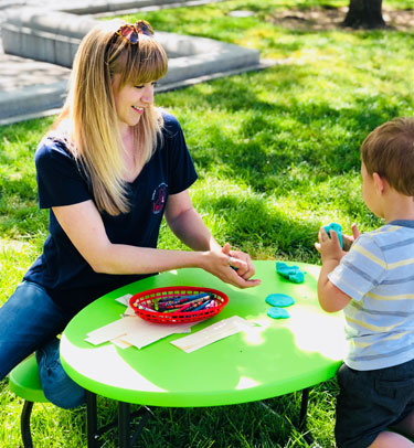 A childcare worker plays with a boy at a small table