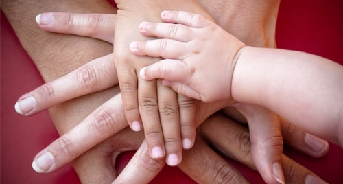 Hands of all ages stacked on top of one another. The top hand is a toddler's.