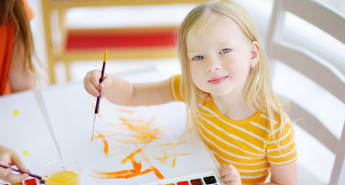A young child is painting with watercolor.