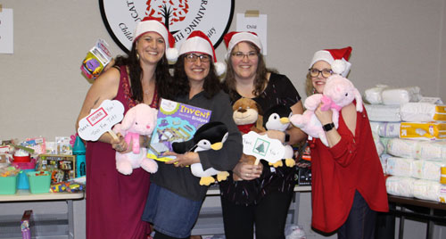 A group of volunteers show off donations made around the holidays,