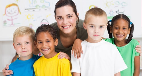 A young caregiver poses for a photo with her kids of varying ages and ethnicities.