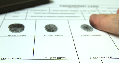 A photo of paper with black ink fingerprints.