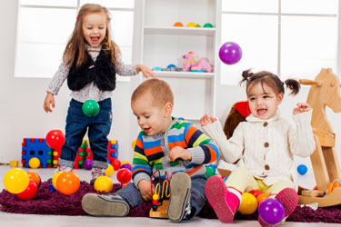 Three young children play with colored balls while sitting on the floor.