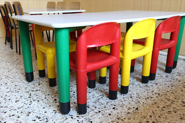colorful plastic chairs seated around a child's table.
